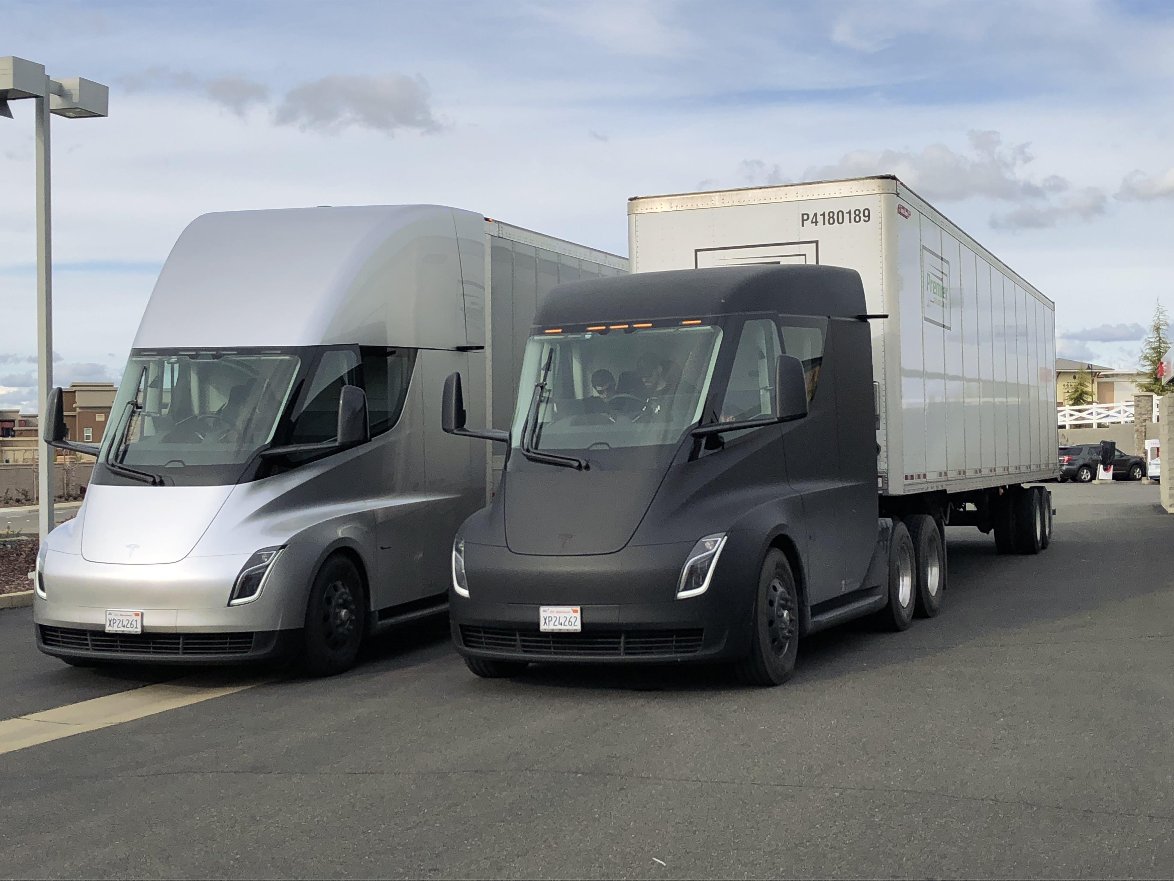 To Tesla Semi ved en ladestasjon.
