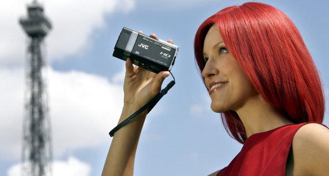 Messemaskoten Miss IFA filmer med  JVCs nye videokamera GZ-X900. I bakgrunnen IFAs landemerke, radiotårnet Funturm.
