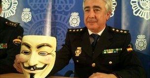 En representant for spansk politi viser stolt fram en Anonymous-maske som skal ha blitt beslaglagt hos en av de tre arresterte.