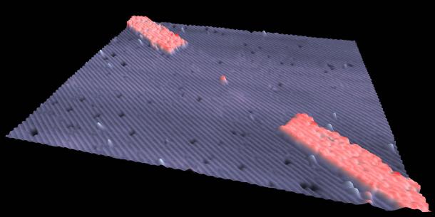 Dette er en transistor på størrelse med ett atom. De røde områdene er elektriske ledere.