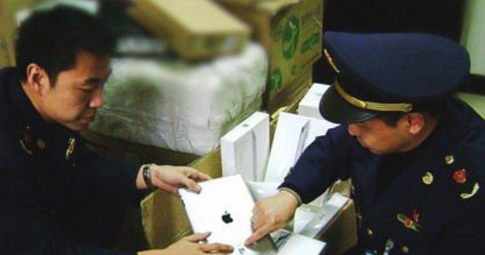 Dette bildet fra februar i år viser hvordan kinesisk politi fjerner iPad fra butikkhyllene.