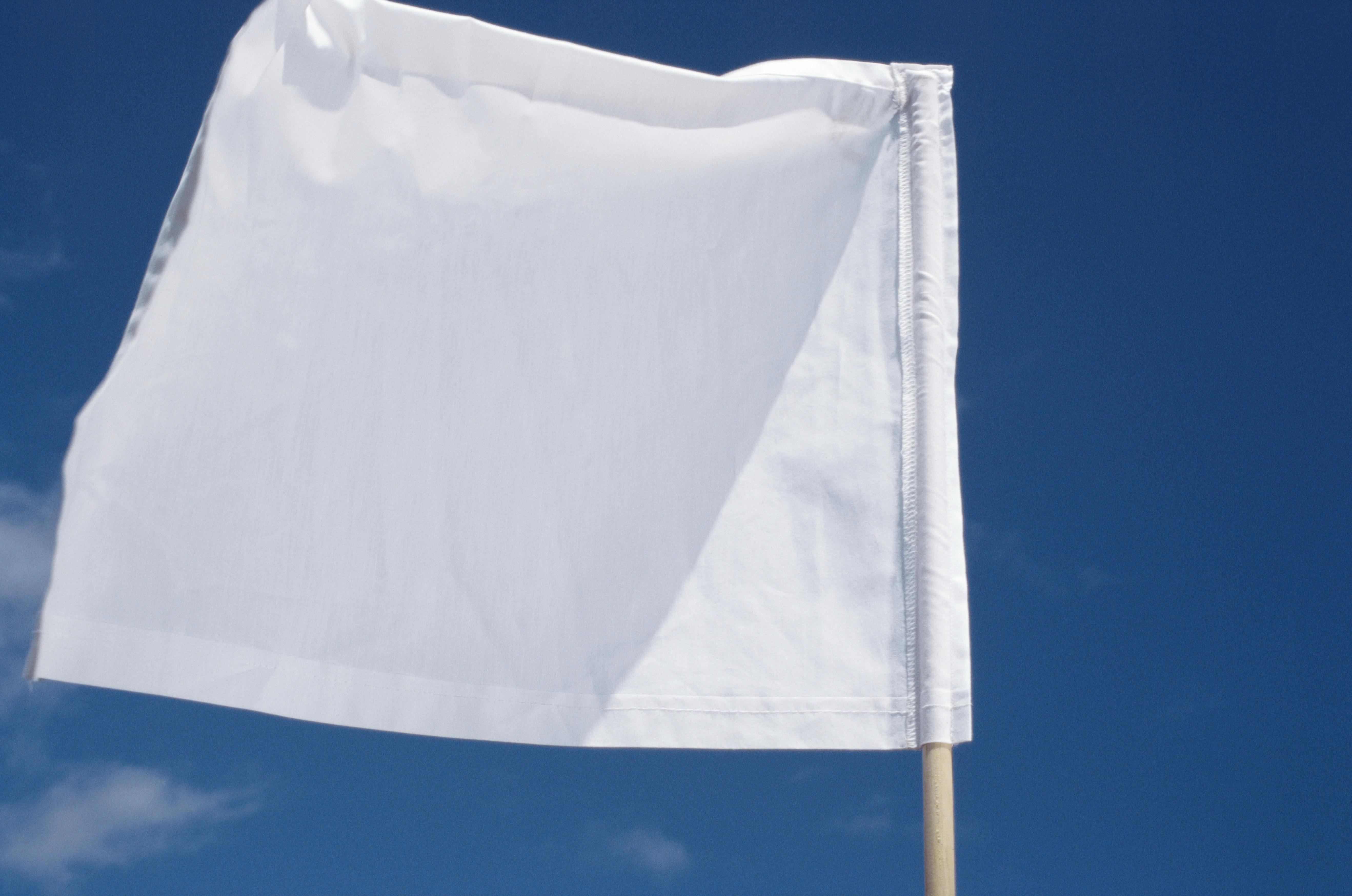 Close up of a white flag against blue sky